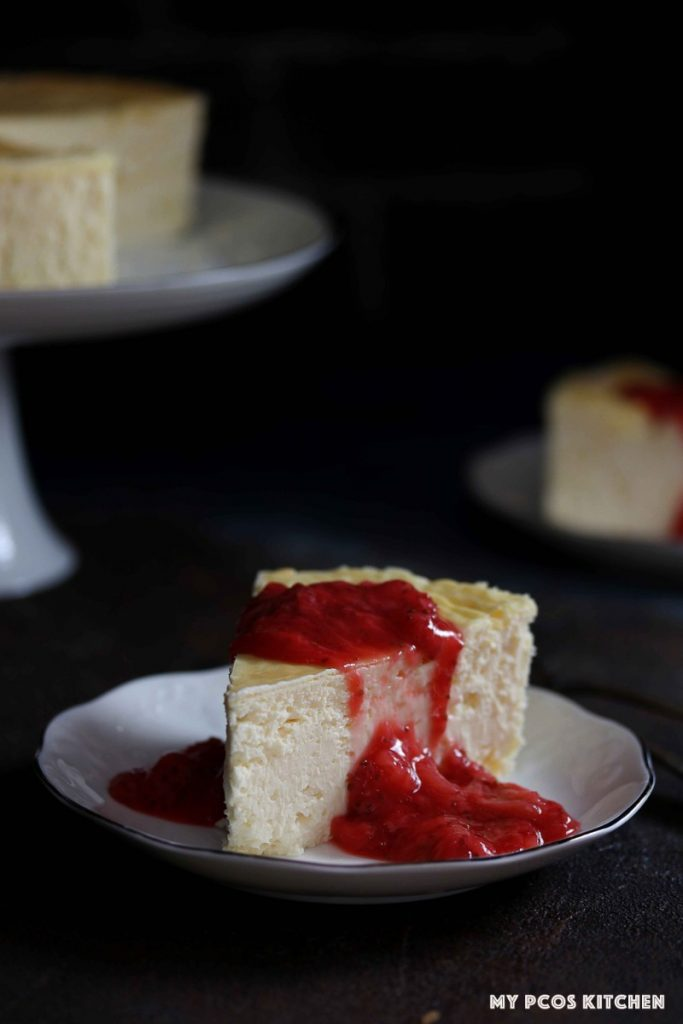 A low carb cheesecake sliced covered in a sugar free strawberry sauce.