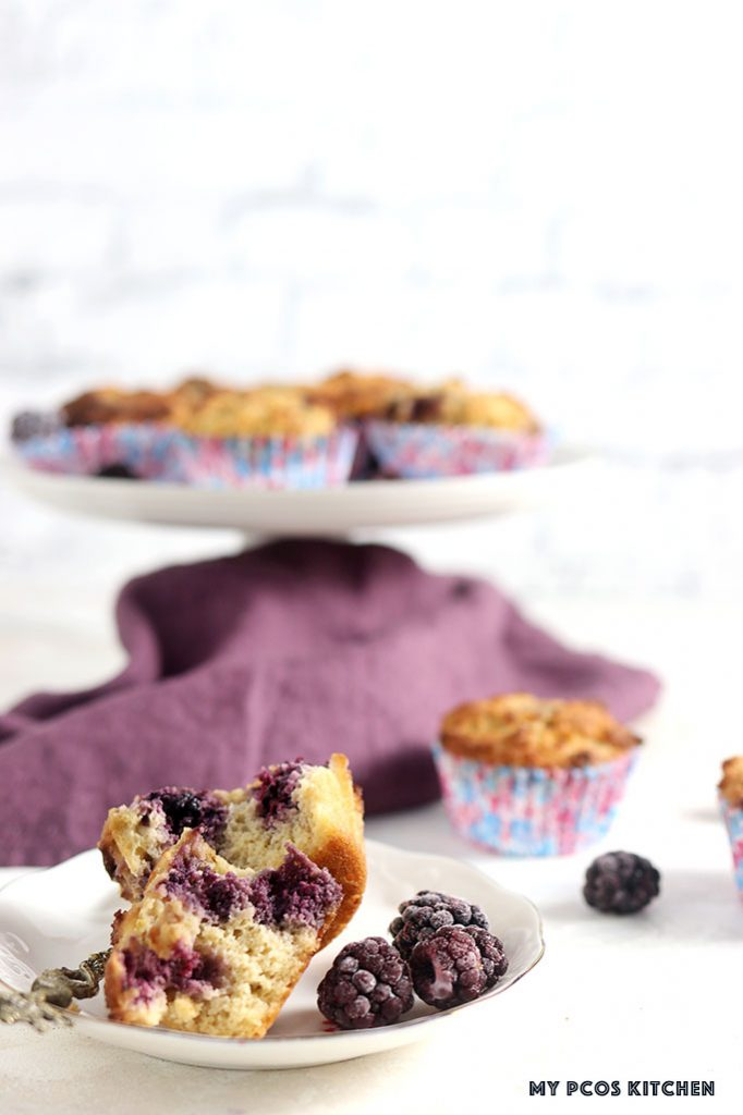 A low carb muffin filled with blackberries on a plate split in half.