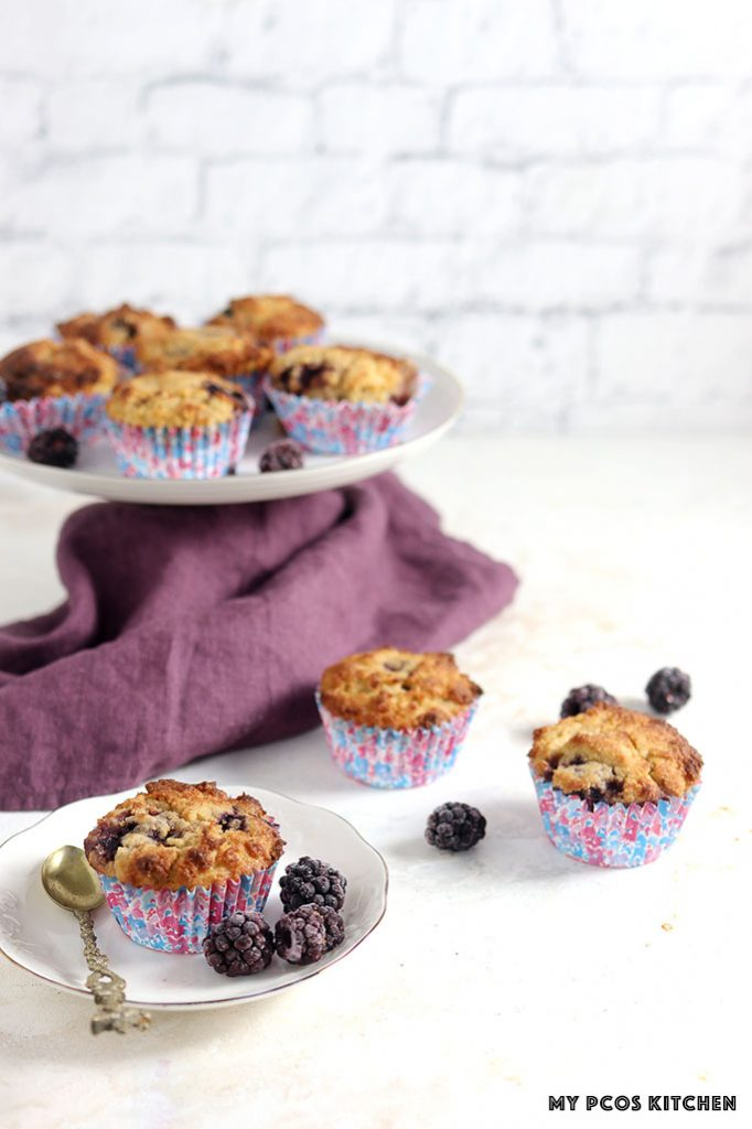 Healthy blackberry muffins in muffin cups and over a cake stand.
