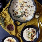 A staub cast iron skillet filled with creamy cauliflower soup.