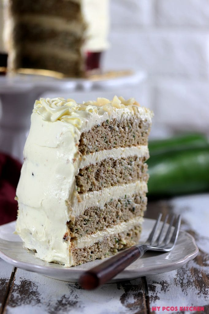 A four layer zucchini cake slice on a plate with a fork beside.