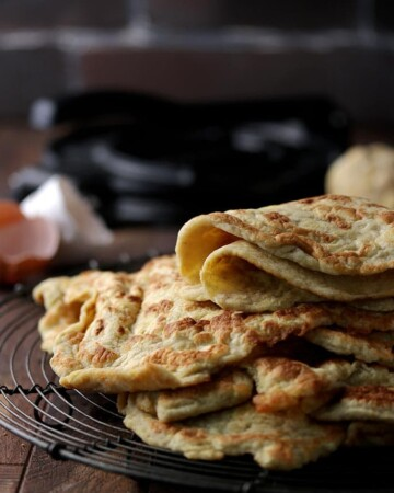 These soft keto tortillas are folded in half over a stack of other low carb tortillas.