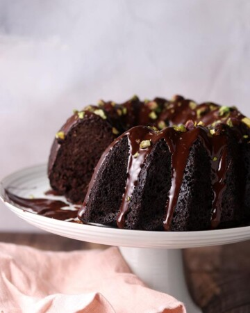 A dairy free keto chocolate cake made in a bundt mold covered in sugar free chocolate.