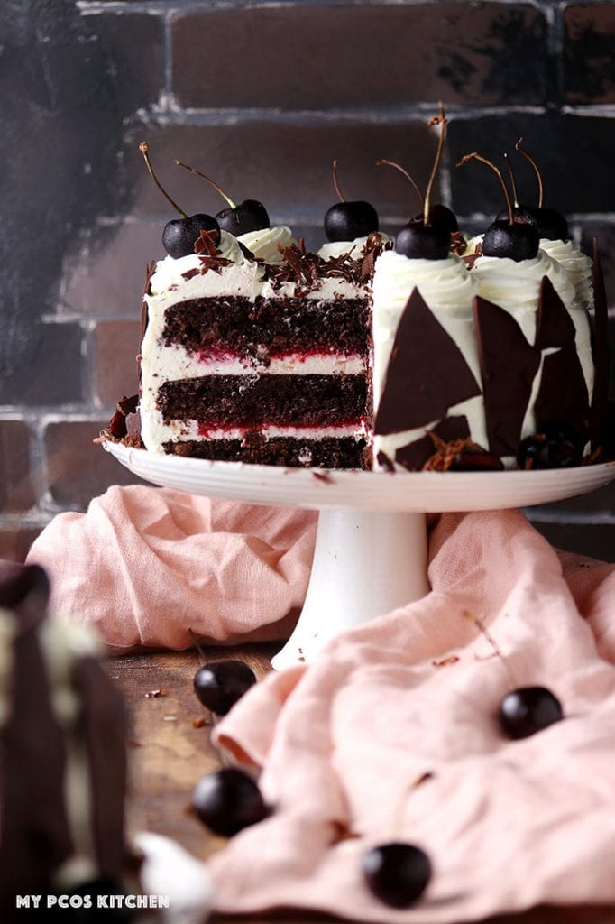 A keto black forest chocolate cake on a cake stand with fresh cherries.