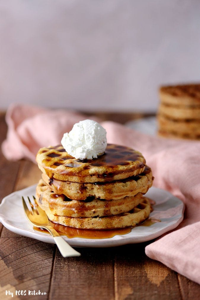 A stack of dairy free low carb waffles with keto maple syrup and coconut whipped cream on top.