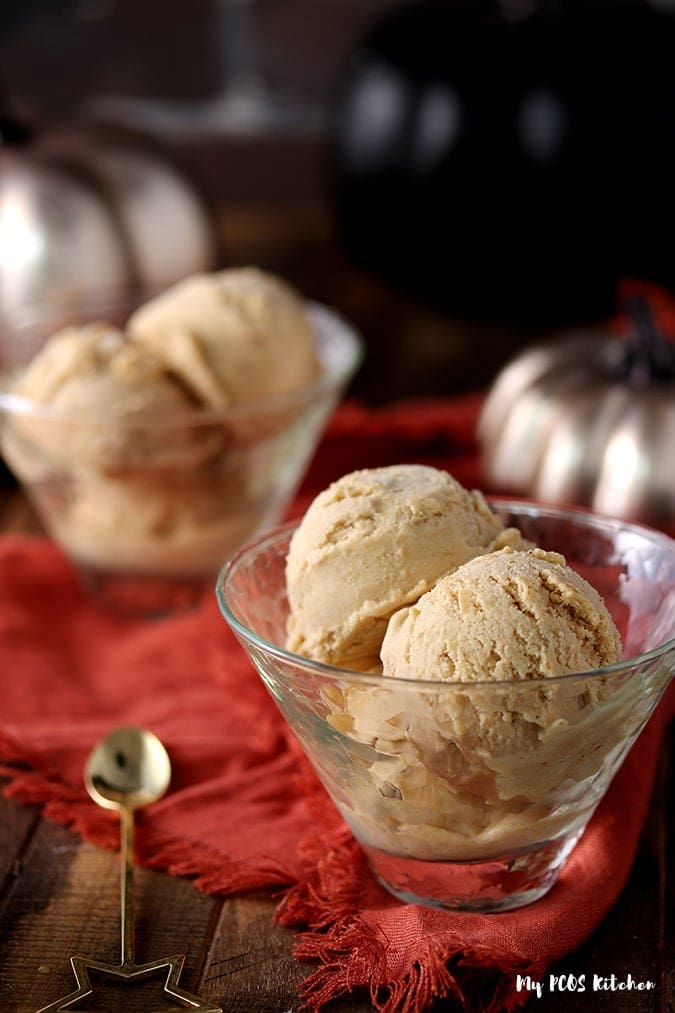 Keto pumpkin ice cream scoops inside glass bowls served on a wooden table.