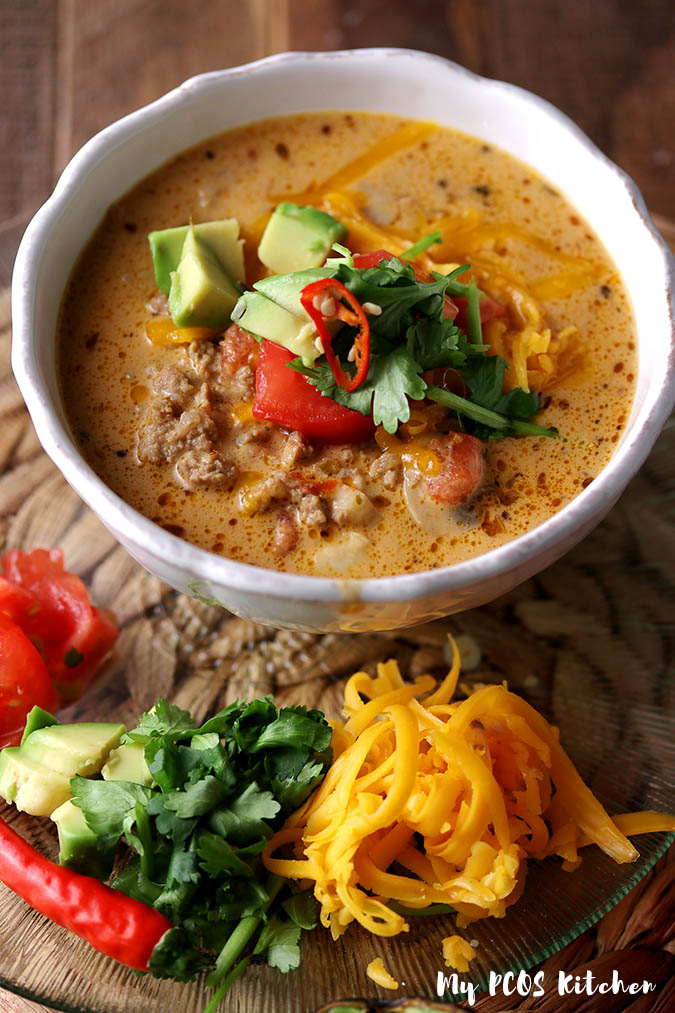 An easy keto taco soup recipe topped with low carb taco toppings serve in a white bowl.