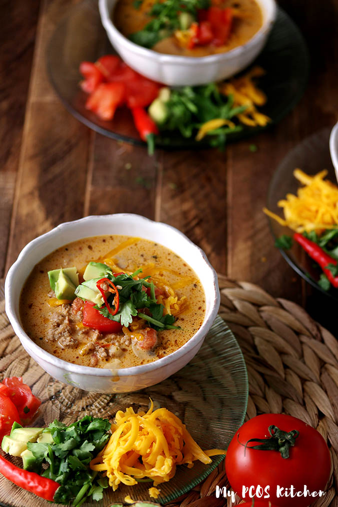 A bowl filled with cheesy taco soup with taco ingredients on the side.
