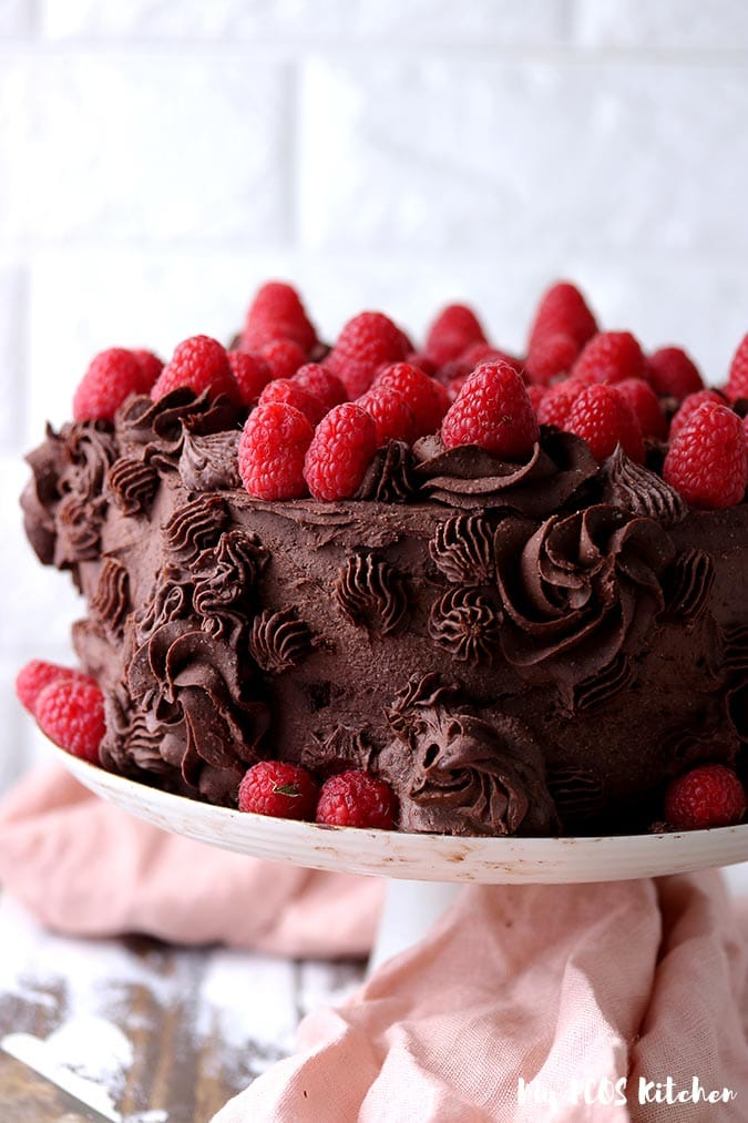 A keto chocolate cake filled with raspberries coated with a keto chocolate frosting recipe.
