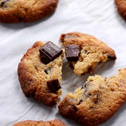 A chewy keto chocolate chip cookie gently split in 3 with melted sugar free chocolate bars on top.