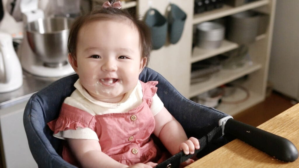A baby smiling after eating some keto cauliflower cheese.
