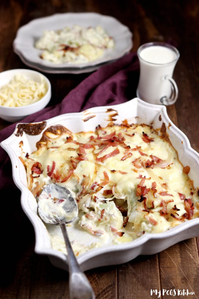 A white baking dish showing baked cauliflower au gratin with a serving on a white plate.