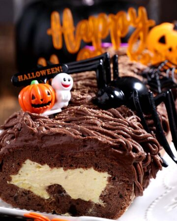 A keto gluten free swiss roll filled with pumpkin cream and chocolate frosting decorated with halloween props.