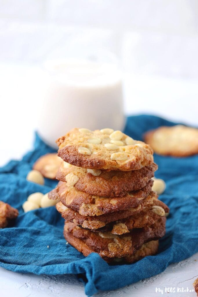 A stack of keto white chocolate macadamia cookies with a glass of  almond milk in the background.